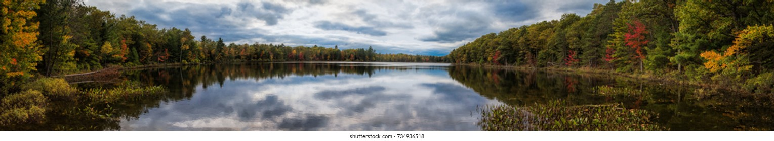Panorama fall scene with colorful leaf reflections on Lake Mcgrath. Wisconsin.