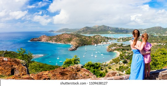 Panorama of family mother and daughter enjoying aerial view of picturesque English Harbour at Antigua and Barbuda in Caribbean