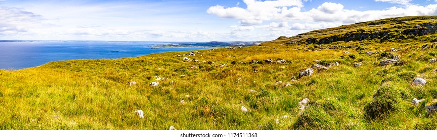 Panorama of farm field in Burren way trail with Galway bay in background, Ballyvaughan, Clare, Ireland