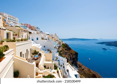 Panorama of Fira with whitewashed buildings carved into the rock on the edge of the caldera cliff on the island of Thira (Santorini), Greece.