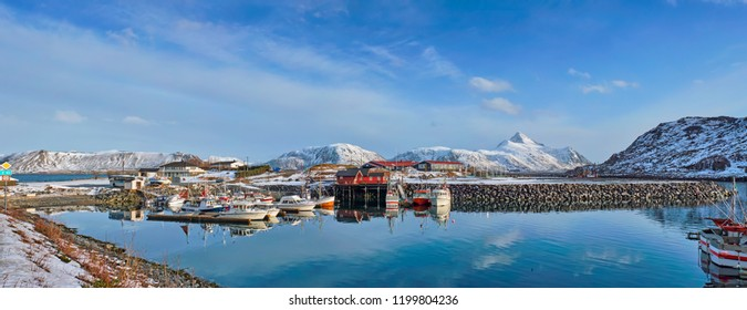 Panorama of fishing boats and yachts on pier in Norwegian fjord in village on Lofoten islands in winter, Norway