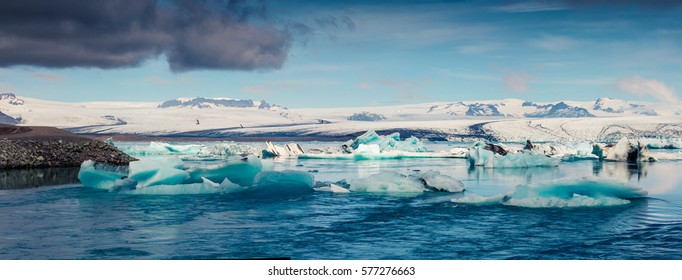 Panorama of floating of blue icebergs in Jokulsarlon glacial lagoon. Dramatic summer morning in Vatnajokull National Park, southeast Iceland, Europe. Artistic style post processed photo.