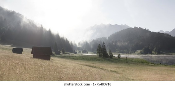 Panorama of foggy morning in the mountains - meadow and hut near Lake Gerold