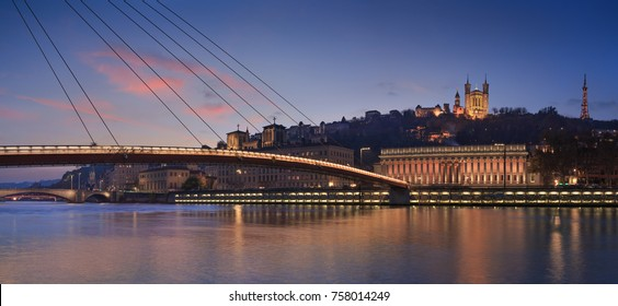 Panorama of a footbridge over the Saone river in Lyon, France, during twilight.