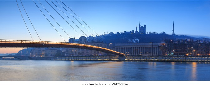 Panorama of footbridge Passerelle Palais du Justice over the Saone river in Lyon, France, during twilight.