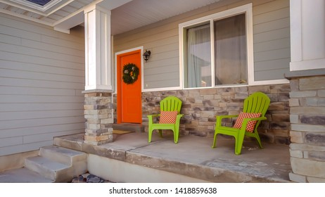 Panorama frame Facade of home with bright orange front door decorated with a festive wreath