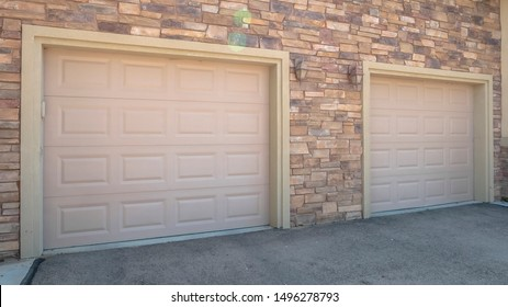 Panorama frame White garage doors of a home against exterior wall covered with stone bricks