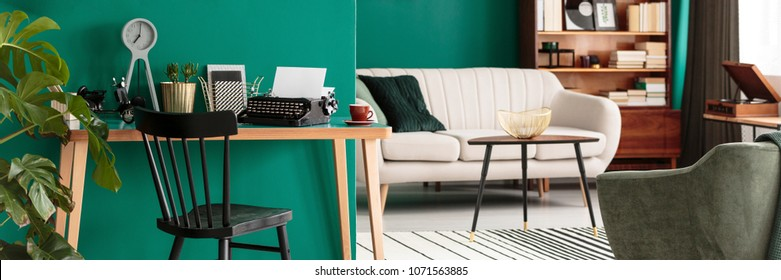 Panorama of a freelance writer's workspace with a desk and typewriter in a teal living room interior with books and elegant furniture