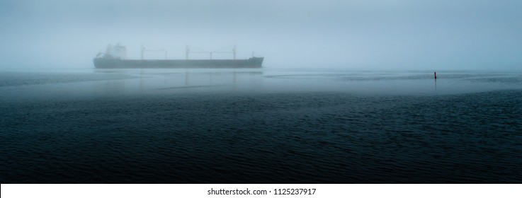 Panorama of a freight ship travelling on a river near a marker bouy during a foggy morning.