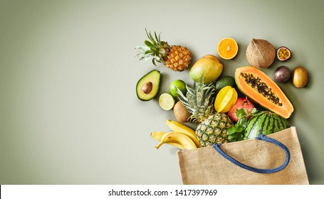 Panorama of fresh juicy tropical fruit overflowing from a reusable shopping bag onto a green background with copy space conceptual of a heathy vegetarian diet and nutrition