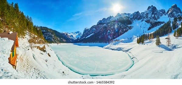 Panorama of the frozen Gosausee lake with fluffy snowy banks and Alps of Dachstein West around it, Salzkammergut, Austria.