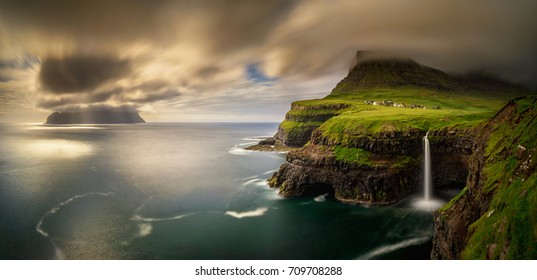 Panorama of Gasadalur village and cloudy Mykines island in sunset, Faroe Islands