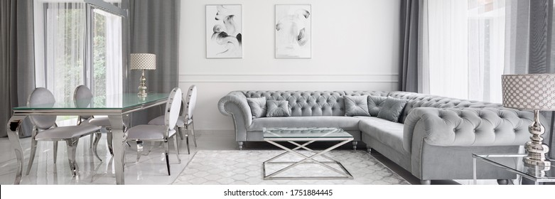 Panorama of glamour designed living room in white and gray with elegant quilted corner sofa and glass dining table