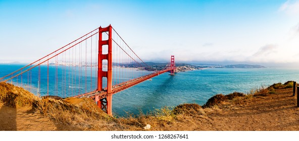 Panorama of Golden Gate Bridge from Marin Headlands Vista point during sunset with the city of San Francisco in the background.