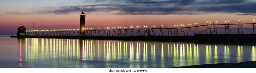 Panorama of Grand Haven Lighthouse at sunset with catwalk lights reflected in Lake Michigan