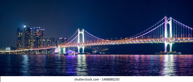 Panorama of Gwangan Bridge and skyscrapers illuminated in the night. Busan, South Korea