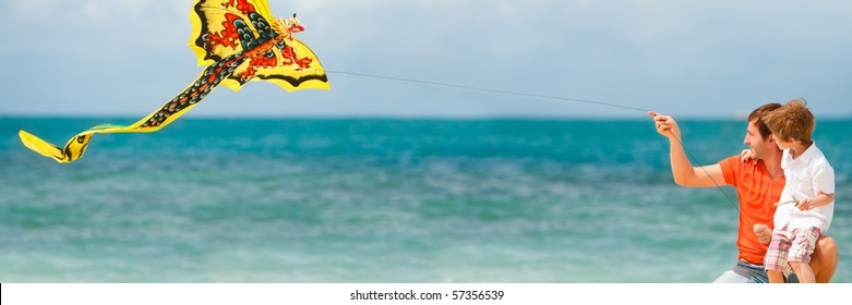 Panorama of happy dad and son flying a kite together