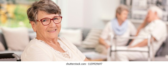Panorama of happy elderly woman in the nursing house. Blurred seniors in the background