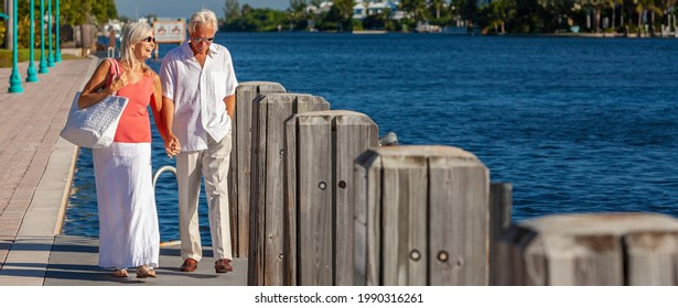 Panorama happy senior man and woman couple together holding hands walking on a jetty or boardwalk by a blue sea in a tropical resort panoramic web banner