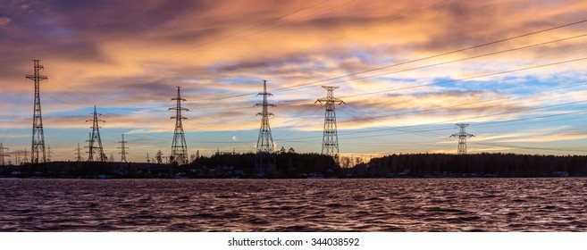 Panorama of high voltage power lines near water at sunset