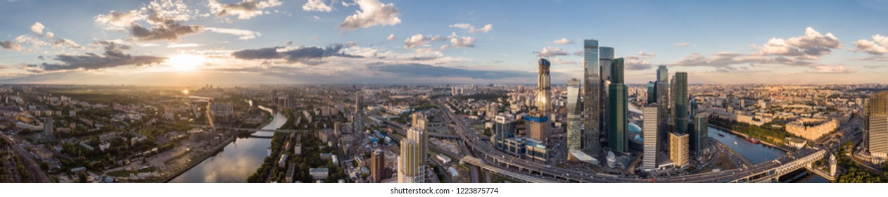 panorama high-rise buildings and transport of metropolis, traffic and blurry lights of cars on multi-lane highways and road junction at sunset in Moscow.