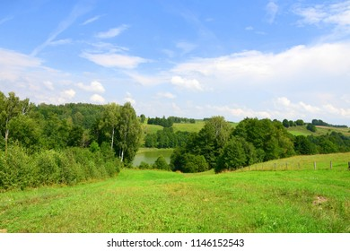 Panorama of hills covered with grass and forest covering them on both sides with a small pond visible in the distance next to some more hills and a cloudy summer sky in Poland