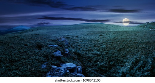 panorama of the hillside meadow at night in full moon light. lovely summer landscape with boulders among the grass. location Runa mountain, Ukraine