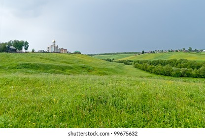 Panorama of hilly landscape with church in background.
