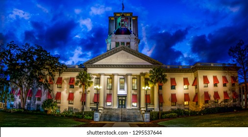 Panorama of historic Florida Statehouse in Tallahassee with iconic red and white awnings illuminated during cloudy sunset with modern capital skyscraper structure in the background