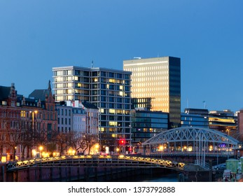 Panorama of historic houses next to modern office buildings with facades of glass reflecting sunset