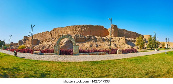 Panorama of historical Ghal'eh Jalali fortress with tall wall, preserved round towers and mud hill, surrounded by lawn of Mellat park, Kashan, Iran
