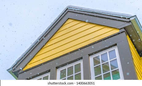 Panorama Home with yellow wall and glass windows against cloudy sky in Daybreak Utah