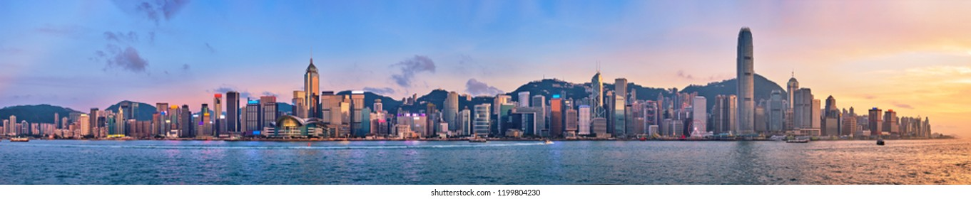 Panorama of Hong Kong skyline cityscape downtown skyscrapers over Victoria Harbour in the evening with junk tourist ferry boat on sunset with dramatic sky. Hong Kong, China