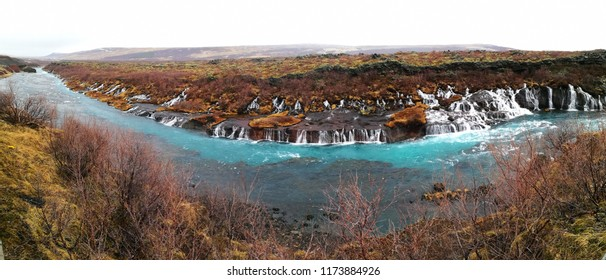 Panorama of Hraunfossar waterfall meets light green turquoise of Hvita river, Iceland