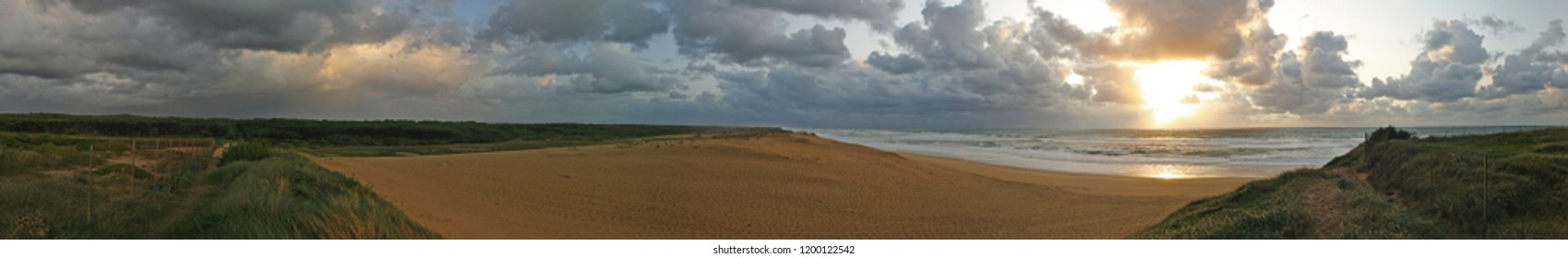 Panorama image of a beach or bay on the atlantic ocean with sand, grass, waves, high rocks and a blue sky with clouds on a sunny day during sunset