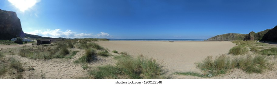 Panorama image of a beach or bay on the atlantic ocean with sand, grass, waves, high rocks and a blue sky with clouds on a sunny day in summer