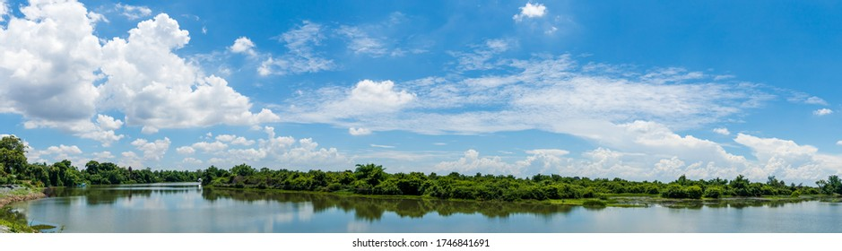 Panorama image, Blue sky, and wispy white clouds on a sunny day over the river.
