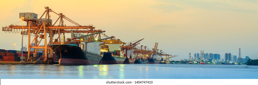 Panorama image of container cargo ship with ports crane bridge in harbor and refinery industrial at night logistics and transportation concept