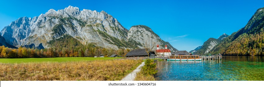 Panorama image of the Koenigssee with the chapel of st bartholomew and a tourist boat. In the background the illuminated mountain formation of Watzmann in bavaria, Germany