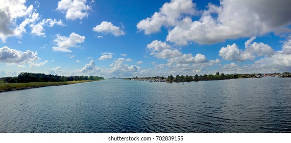 Panorama image of waterway in Denmark, Scandinavia, with blue sky and white clouds