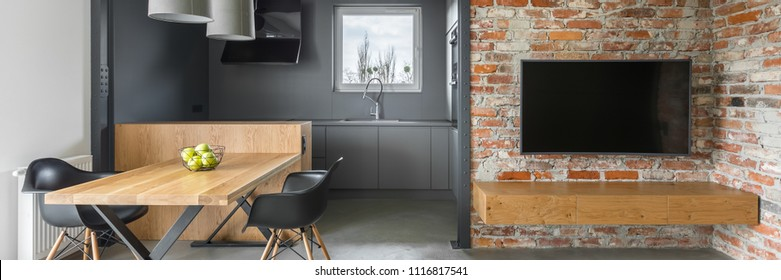 Panorama of industrial style apartment with kitchenette, tv, table, chairs and brick wall