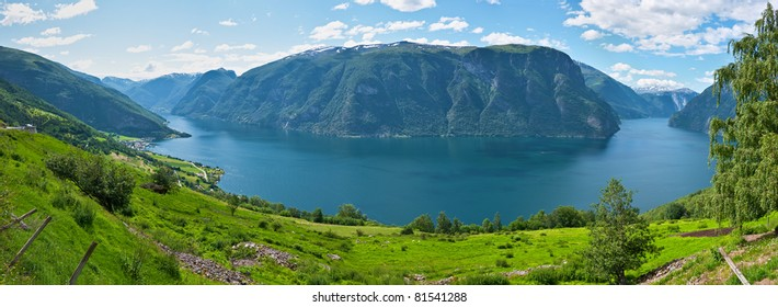 Panorama inner Aurlandsfjord Norway with green hillsides and a view towards the fjord and mountains in the background at summer time