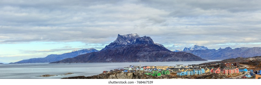 Panorama of �olorful Inuit houses on a coastline in a suburb of Nuuk with Sermitsiaq mountain and fjord in the background, Greenland