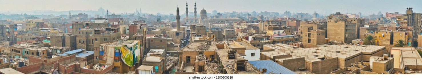 Panorama of Islamic Cairo shabby buildings with garbage on the roofs, Al Muizz market street, Bab Zuwayla historic gate and Saladin Citadel on the horizon, Cairo, Egypt.