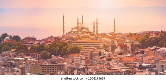 Panorama of Istanbul skyline with imperial mosque at sunset. Sun, sky and mountains in background and city in foreground