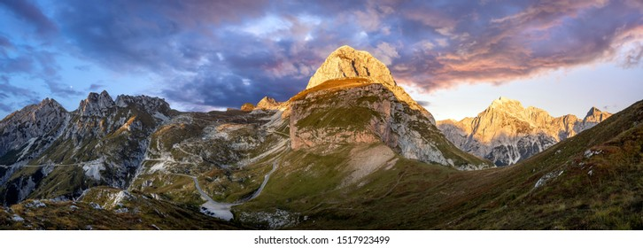 Panorama of the Julian Alps. The peak of Mangart, a road on the pass leading to the mountain shelter under Mangart