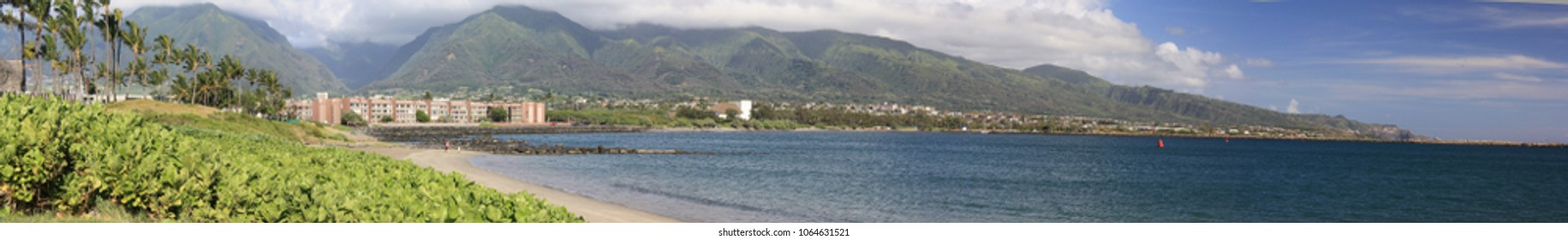 panorama of Kahului Harbor with condos/houses/hotels against a volcano with cloud cover