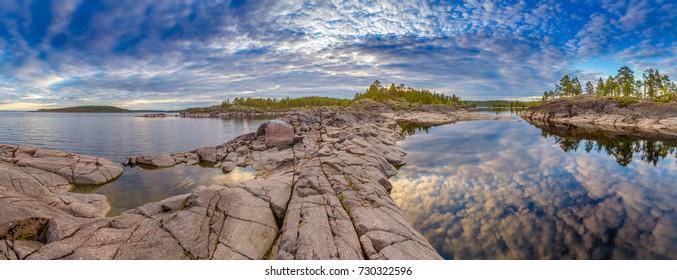 Panorama of Karelia. Ladoga lake. Karelia. Russia. Reflection of clouds in the water. Stuck stones.