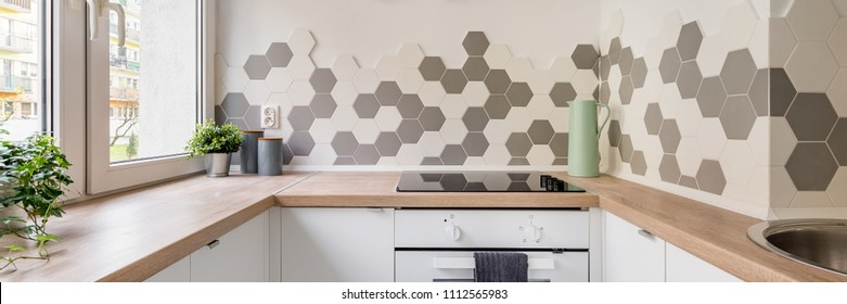 Panorama of kitchen in scandinavian style with white cabinets, wooden countertop and hexagonal wall tiles