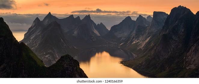 Panorama of Kjerkfjorden among dramatic mountain ridges in sunset light, Lofoten